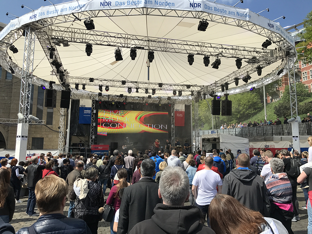 Picture of outdoor concert with many spectators at the front of the stage